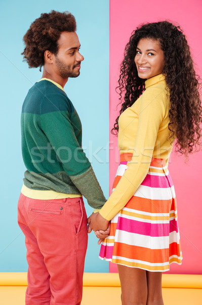 Cheerful african young couple smiling and holding hands Stock photo © deandrobot
