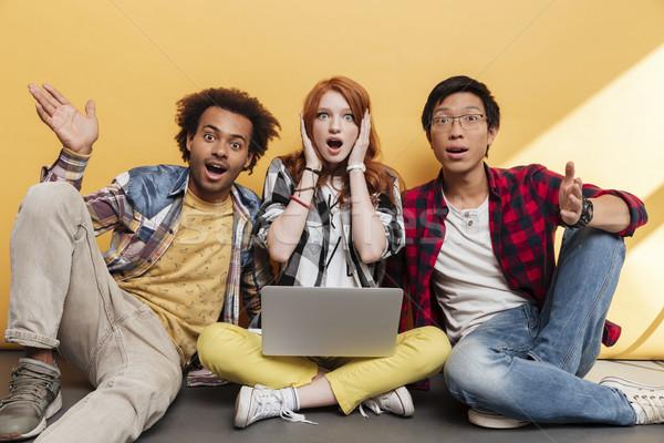 Três maravilhado jovens sessão usando laptop amarelo Foto stock © deandrobot