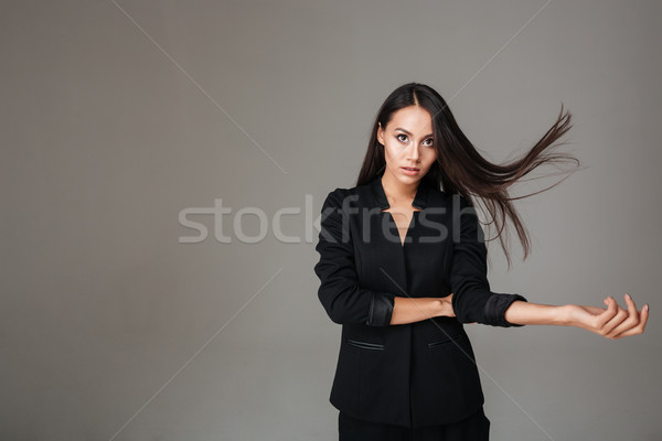 Genç esmer kadın siyah takım elbise ayakta uçan Stok fotoğraf © deandrobot