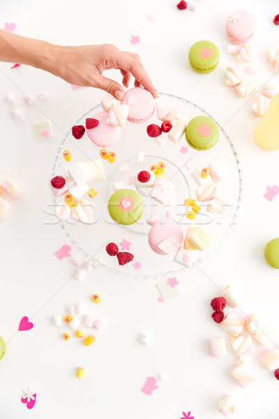 Top view of hand taking macaroon from plate with desserts Stock photo © deandrobot