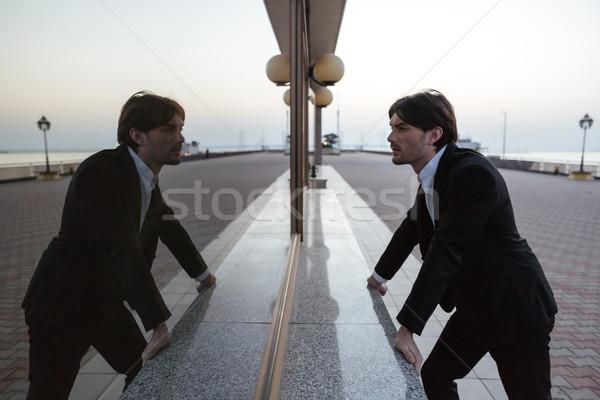 Biznesmen portu garnitur patrząc lustra świetle Zdjęcia stock © deandrobot