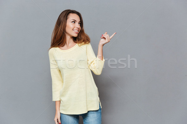 Portrait of a smiling woman in sweater pointing finger away Stock photo © deandrobot