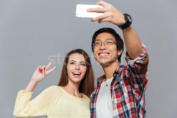 Portrait of a smiling interracial couple making selfie together Stock photo © deandrobot