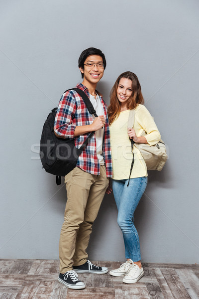 Full length portrait of a interracial couple standing with backpacks Stock photo © deandrobot