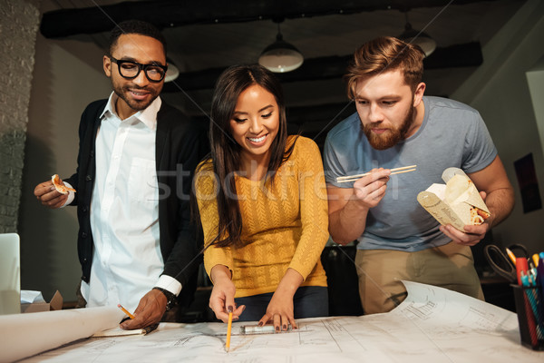 Happy architects working at night while looking on project Stock photo © deandrobot