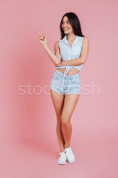 Smiling young woman standing and pointing finger away at copyspace Stock photo © deandrobot