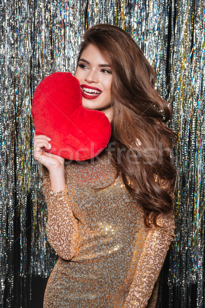Smiling attractive young woman holding red heart Stock photo © deandrobot