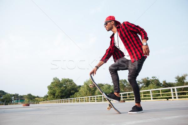 Ciemne człowiek okulary skateboarding zdjęcie Zdjęcia stock © deandrobot