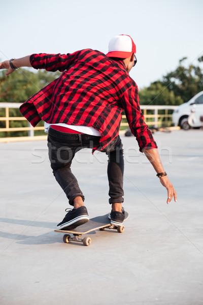 Young dark skinned guy skateboarding Stock photo © deandrobot