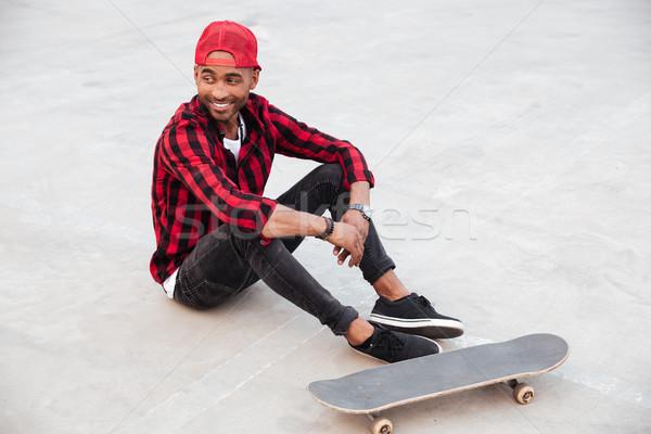 Cheerful dark skinned boy sitting near his skateboard Stock photo © deandrobot