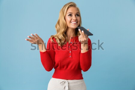 Beautiful smiling woman in red shirt standing with arms folded Stock photo © deandrobot