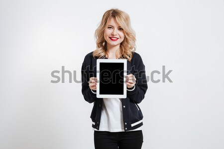 Young lady showing display of tablet computer to camera. Stock photo © deandrobot