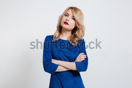 Lady with arms crossed posing over white background. Stock photo © deandrobot