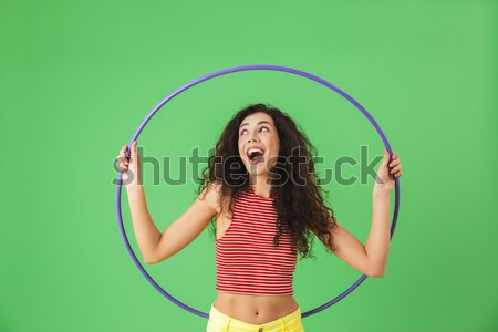 Happy young woman athlete standing and looking through hula hoop Stock photo © deandrobot