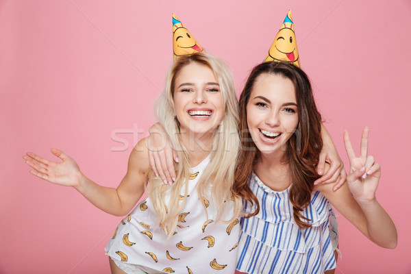 Two cheerful young women in hats hugging and celebrating birthday Stock photo © deandrobot