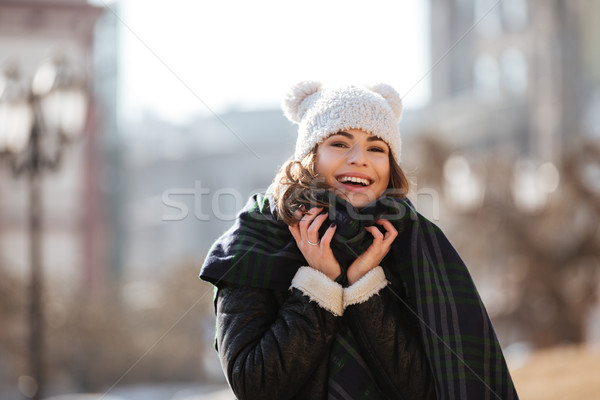 Happy woman in funny hat and scarf standing outdoors Stock photo © deandrobot