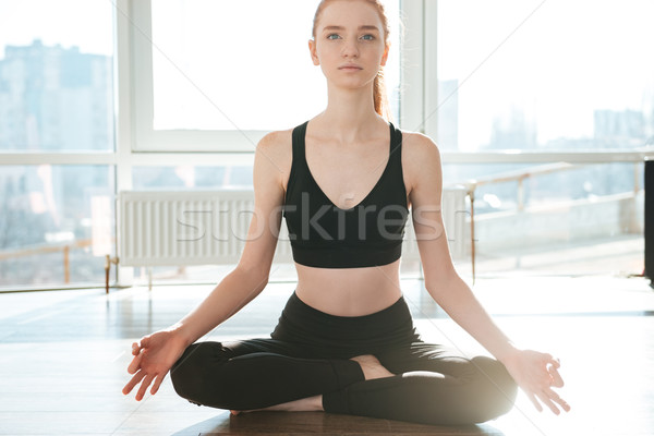 Woman sitting in lotus pose and meditating at yoga studio Stock photo © deandrobot