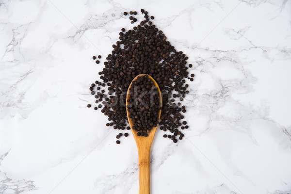 Top view of aa wooden spoon full of black peppercorns Stock photo © deandrobot