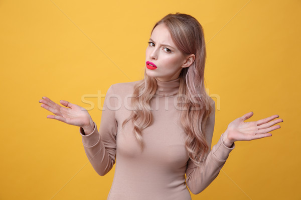 Confused young blonde lady with bright makeup lips Stock photo © deandrobot