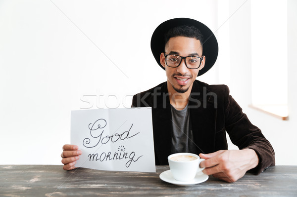 African man with coffee showing sheet of paper Stock photo © deandrobot