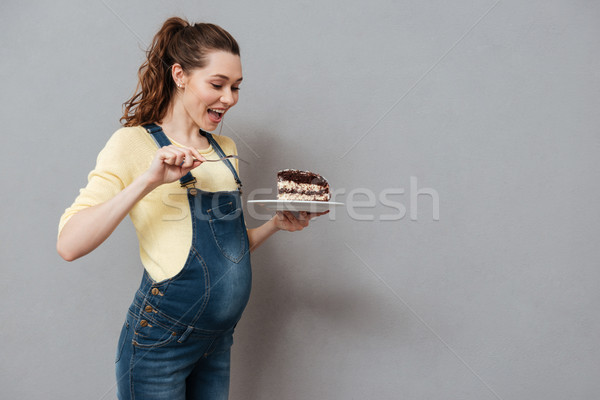 Portrait of an excited young pregnant woman eating chocolate cake Stock photo © deandrobot