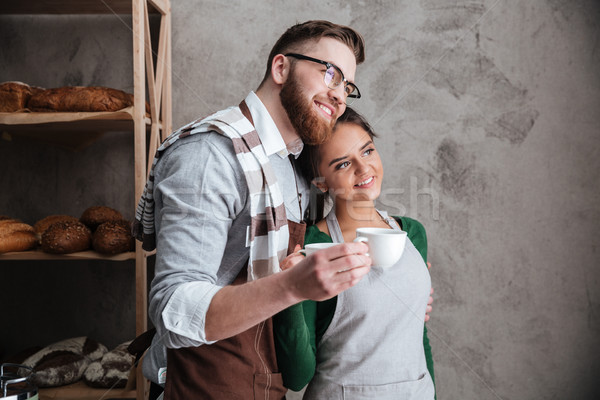 Stock photo: Happy young loving couple bakers drinking coffee.