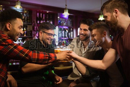 Happy male friends clinking with beer mugs in pub Stock photo © deandrobot