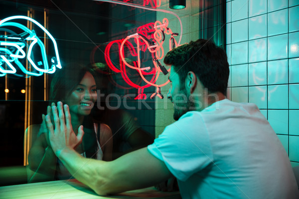 Multiethnic loving couple sitting in cafe looking aside. Stock photo © deandrobot