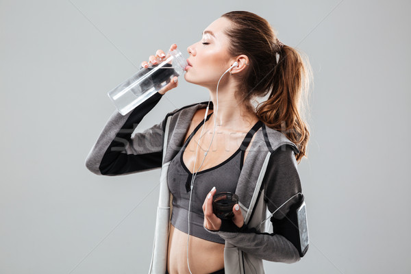 Side view of a tired woman drinking water Stock photo © deandrobot