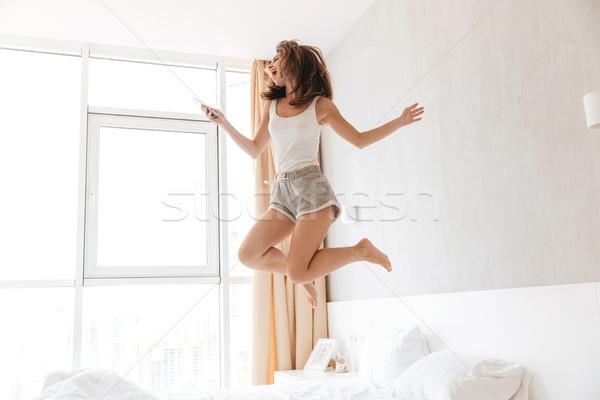 Teljes alakos portré boldog fiatal nő fülhallgató zenét hallgat Stock fotó © deandrobot
