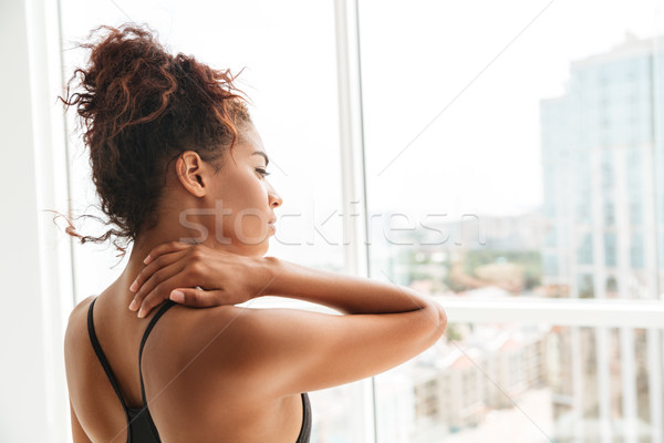 Side view of african beautiful woman looking in window Stock photo © deandrobot