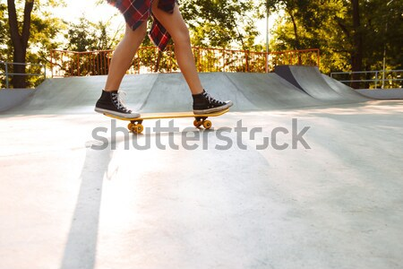 Loving couple on skateboards outdoors. Looking aside. Stock photo © deandrobot