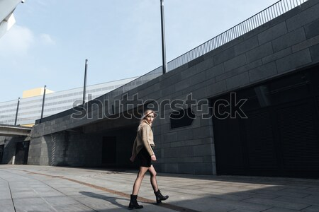 Serious young blonde lady standing with eyes closed outdoors. Stock photo © deandrobot