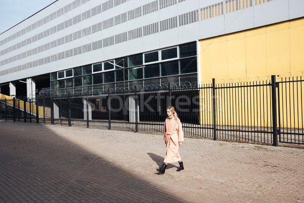 Serious young blonde lady walking outdoors. Looking aside. Stock photo © deandrobot