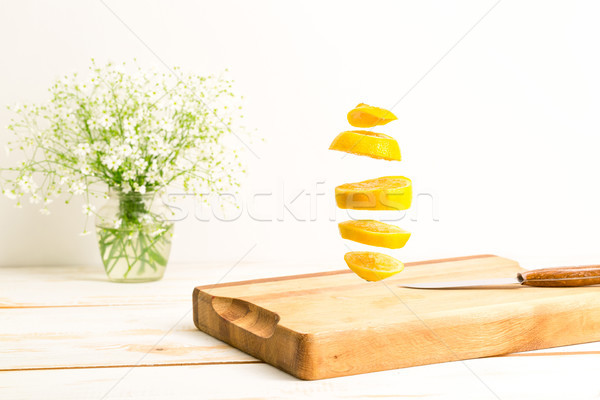 Sliced whole lemon flying above a wooden chopping board Stock photo © deandrobot