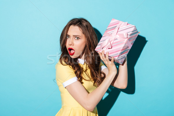Portrait of an astonished girl in dress holding gift box Stock photo © deandrobot