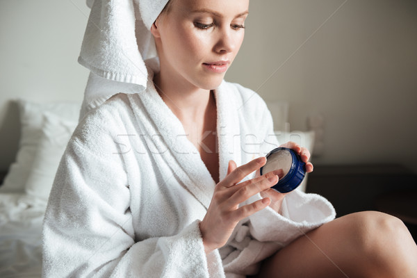 Beautiful young woman wearing white bathrobe applying body lotion Stock photo © deandrobot
