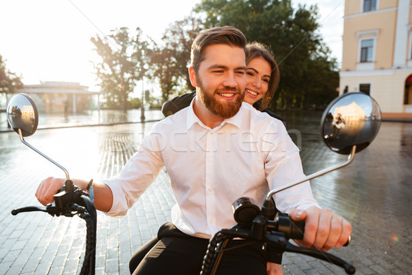 Happy business couple rides on modern motorbike in park Stock photo © deandrobot