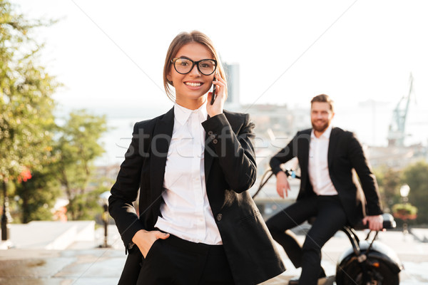 Carefree business woman posing outdoors and talking by smartphone Stock photo © deandrobot