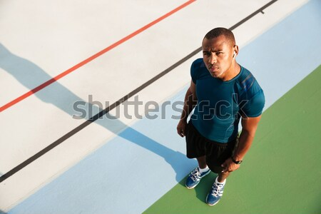 Top view portrait of a young african sportsman doing stretching Stock photo © deandrobot