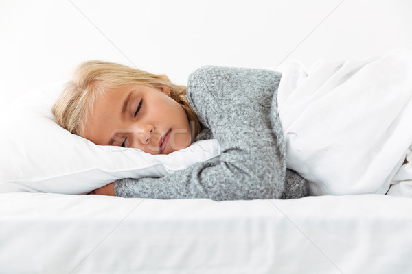 Cute little girl sleeping on white pillow in gray pajamas havin Stock photo © deandrobot