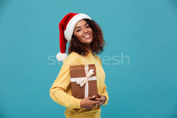 Happy young african lady dressed in warm sweater holding gift Stock photo © deandrobot