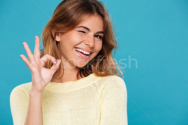 Smiling woman in sweater showing ok sign and winks Stock photo © deandrobot