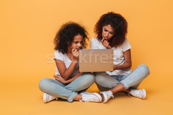Two thoughtful afro american sisters using laptop computer Stock photo © deandrobot