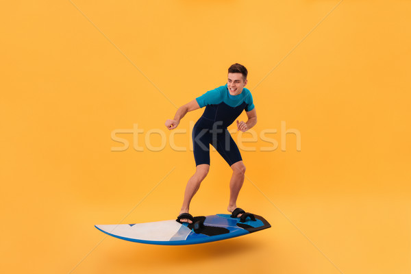 Picture of a Smiling surfer in wetsuit using surfboard Stock photo © deandrobot