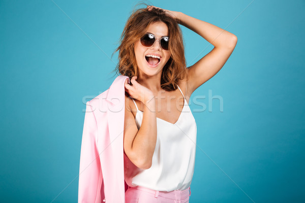 Portrait of a cheerful woman dressed in pink suit Stock photo © deandrobot