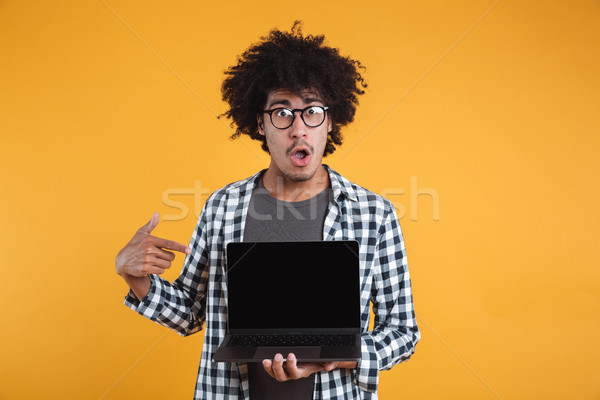 Portrait of a cheerful happy african man in eyeglasses pointing Stock photo © deandrobot