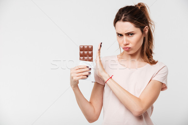 Portrait of a serious girl refusing to eat chocolate bar Stock photo © deandrobot