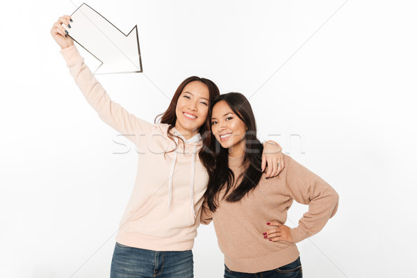 Two asian positive ladies sisters holding arrow. Stock photo © deandrobot