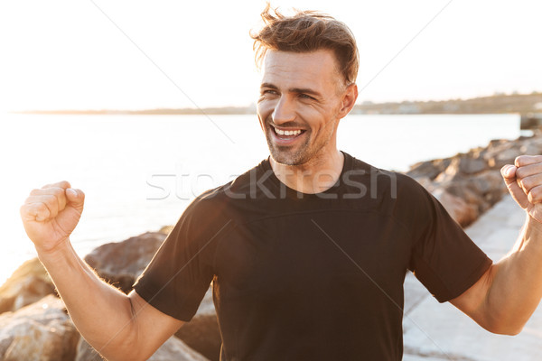 Portrait of a cheerful sportsman Stock photo © deandrobot